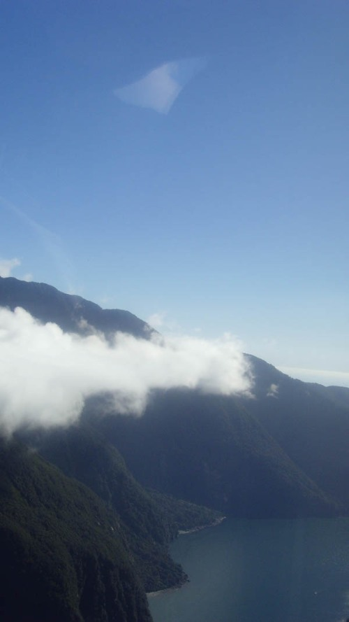 On a remarkably clear day in Milford Sound, a whispy cloud partially covers the mountain as we look out to St Anne Point