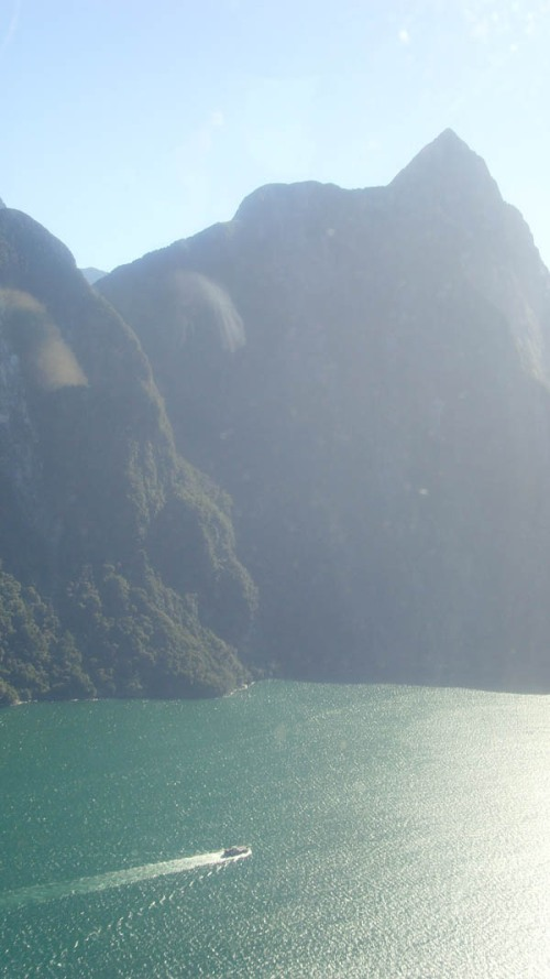 High above Milford Sound - a boat steams out towards the Tasman Sea